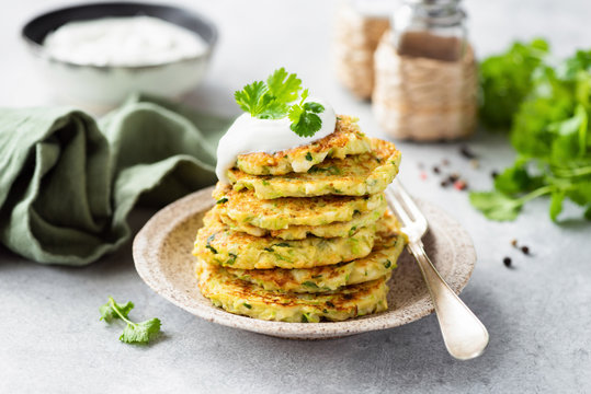 Vegetarian zucchini fritters or pancakes stack topped with sour cream and cilantro. Vegetable pancakes
