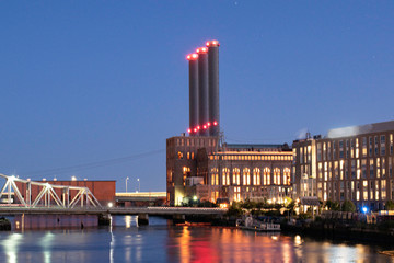 Night Image of Factory and Warehouse In Downtown Skyline From The Providence River Pedestrian Bridge With Long Exposure, Blue Sky and Reflections In River.