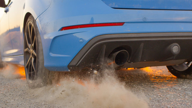 CLOSE UP Car starts and quickly drives away, tires spinning, raising sand & dust