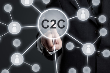 Executive businessman in suit touching C2C button in network with people icons on virtual touch screen -  consumer to consumer networking concept