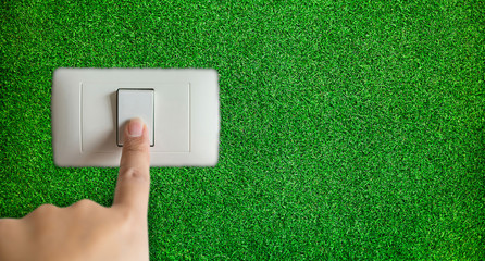 Concept of save energy use efficiency. Hand turning off switch with grass background