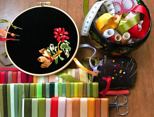 The process of embroidery with satin ribbons a floral ornament in red, golden and green color on black velvet (embroidery made author of photo). Accessories for embroidery, needles and sets of ribbons