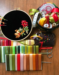 The process of hand embroidery with red, gold and green satin ribbons on black velvet and accessories for embroidery (embroidery was made by the author of the photo)