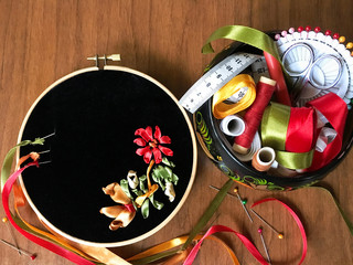 The process of embroidery with red, gold and green satin ribbons on black velvet and a box with accessories for needlework (embroidery was made by the author of the photo). Place for text, flat lay