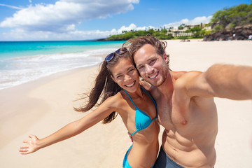 Wall Mural - Happy beach couple selfie having fun smiling on Hawaii vacation suntan fit body Asian bikini girl excited with open arms smiling, man taking photo with phone.