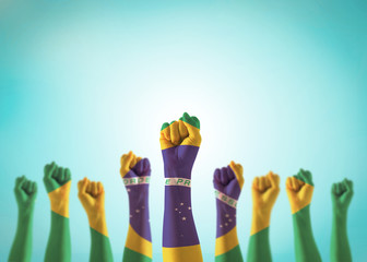 Photo sur Aluminium Brésil Brazil flag on people hands with clenched fists raising up for labor day national holiday celebration and stay strong for Brazilian power isolated on blue sky background (clipping path)