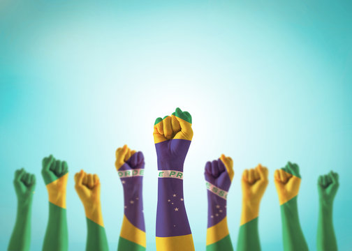 Brazil flag on people hands with clenched fists raising up for labor day national holiday celebration and stay strong for Brazilian power isolated on blue sky background (clipping path)