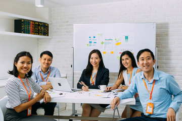 Group portrait of Asian business men and women smiling and looking at camera at company meeting room. Young business people at presentation together. Fototapete