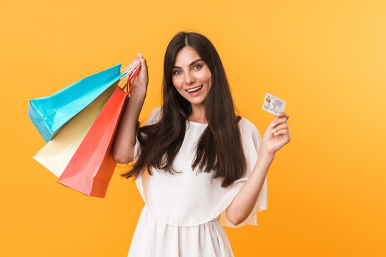 Portrait of elegant shopaholic woman wearing dress holding credit card and colorful shopping bags