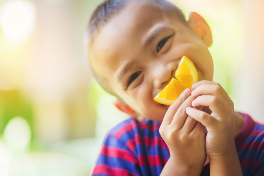 Little asian boy use a slice of orange for smiling face