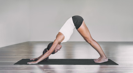 Downward facing dog Asian woman doing yoga pose on black exercise mat in fitness class. Indoor gym studio teacher girl practicing sun salutation routine. Wall mural