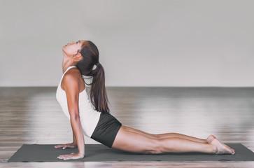 Asian woman stretching lower back with yoga cobra pose on exercise mat. Upward facing dog backbend pose yoga girl. Urdhva mukha svanasana exercise Yoga stretch practice for weight loss.