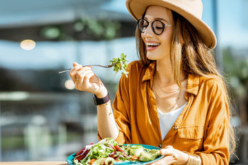 Zelfklevend Fotobehang Kruidenierswinkel Stylish young woman eating healthy salad on a restaurant terrace, feeling happy on a summer day