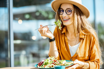 Stylish young woman eating healthy salad on a restaurant terrace, feeling happy on a summer day