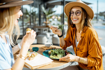 Two female best friends eating healthy food while sitting together on a restaurant terrace on a summer day