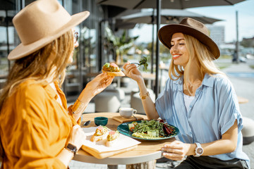 Foto op Canvas Kruidenierswinkel Two female best friends eating healthy food while sitting together on a restaurant terrace on a summer day