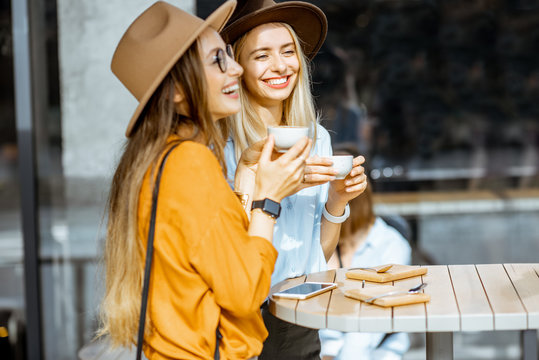 Two female best friends spending time together on the cafe terrace, feeling happy, enjoying coffee during a summer day