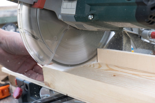 Close-up of a carpenter working with a miter saw. Concept of construction, woodwork, carpentry