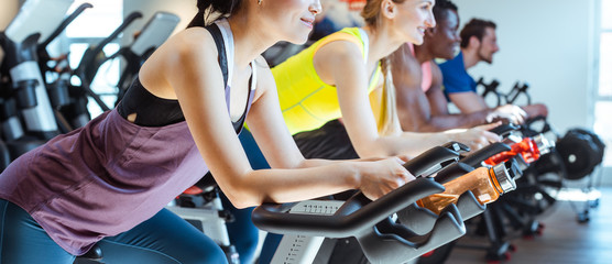 Photo on textile frame Fitness Asian woman and her friends on fitness bike in gym