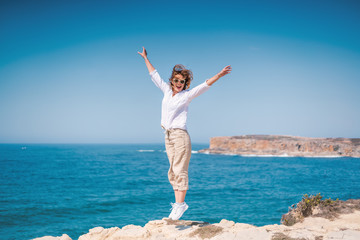 Fototapete - Beautiful young woman with a happy smile in a white shirt on the ocean in Portugal