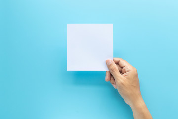 man hand holding blank card paper sheet isolated on blue background with copy space. Wall mural