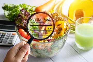 Nourriture nutritional information concept. hand use the magnifying glass to zoom in to see the details of the nutrition facts from food , salad bowl