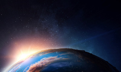 Earth with sunrise on blue space background Wall mural