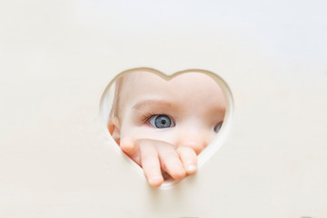 baby face, eyes and hand peep out of a heart-shaped hole in the center. A child looks into the camera through a heart hole. Love and health concept, mock up, poster,