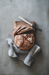 Flat-lay of freshly baked sourdough bread loaf and bread slices on rustic wooden board over grey concrete table background, top view, vertical composition