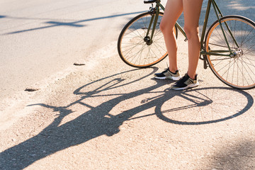 Cropped image of caucasian woman riding bicycle through city street on summer sunny day