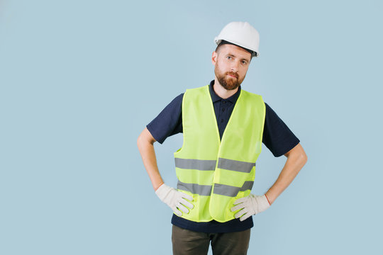 Confident construction worker in a white helmet and yellow safety vest