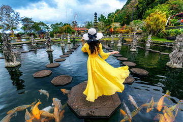 Woman standing in pond with colorful fish at Tirta Gangga Water Palace in Bali, Indonesia.