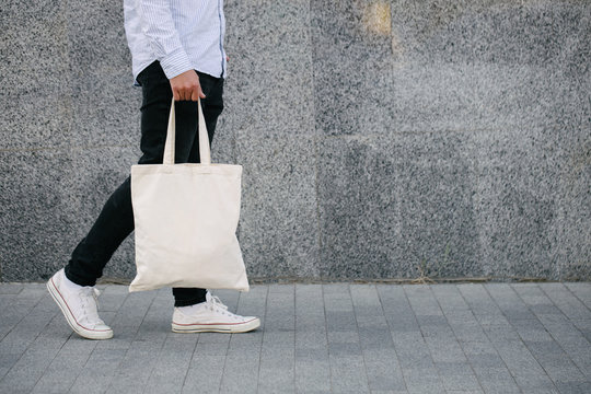 Young man holding white textile eco bag against urban city background. . Ecology or environment protection concept. White eco bag for mock up.