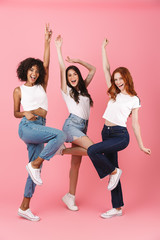 Multi-ethnic girls friends posing isolated over pink wall background make winner gesture.