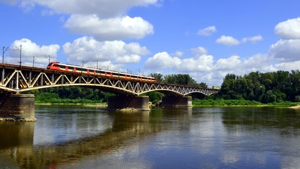 The red train crossing the Srednicowy Bridge in Warsaw, Poland. It is a railway bridge over the...
