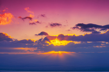 Colorful cloudy sky at sunset. Sunset over the mountains. Pink purple gradient color. Abstract nature background. Sunset sky texture