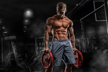 Young male athlete bodybuilder posing and doing sports exercises in the gym Wall mural