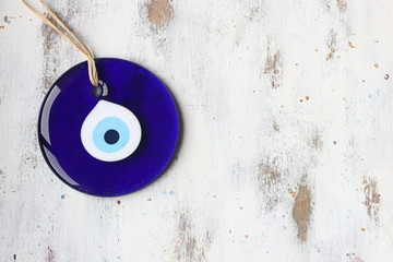 Evil eye bead, Turkish nazar bead on a white wooden background Wall mural