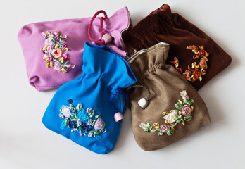 Four handmade cosmetic bags with embroidery with satin and nylon ribbons on a light background. Holiday gifts (bags sewn and embroidered by the author of the photo).