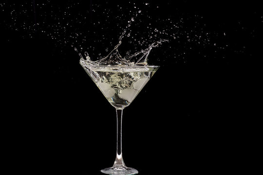 glass of martini and splash from falling ice on a black background