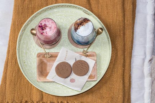 Dos tipos de té matcha servido en bandeja con acompañamiento de dos galletas de chocolate y té verde matcha en su interior.