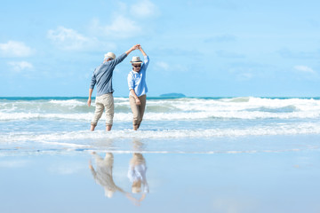 Asian Lifestyle senior couple dancing on the beach happy and relax time.  Tourism elderly family travel leisure and activity after retirement in vacations and summer.