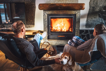 Father with son sitting in comfortable armchairs in their cozy country house near fireplace and enjoying a warm atmosphere and flame moves. Their beagle friend dog sitting beside on white sheepskin.