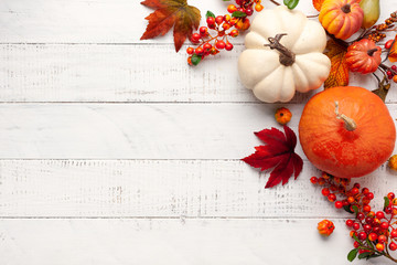 Foto auf Acrylglas Herbst Festive autumn decor from pumpkins, berries and leaves on a white wooden background. Concept of Thanksgiving day or Halloween. Flat lay autumn composition with copy space.