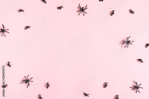 Halloween decorations concept. Halloween with spiders on pastel pink background. Flat lay, top view, copy space
