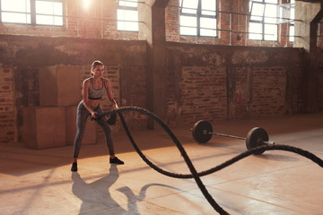 Rope workout. Sport woman doing battle ropes exercise at gym