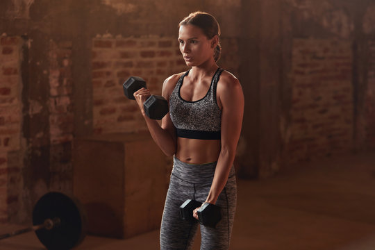 Fitness workout. Woman doing arm exercise with dumbbell at gym
