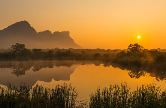 Landscape of the Hanging Lip or Hanglip mountain peak at sunrise with mist hanging above a swamp lake inside the Entabeni Safari Game Reserve, Limpopo Province, South Africa.