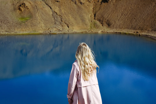 Viti Crater  lake  in Iceland. Young woman traveller on the top of the crater