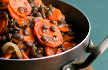 Close up cooked carrots and lentils in pan